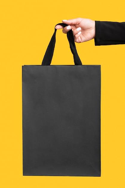 Pessoa segurando uma grande sacola de compras preta Foto Premium
