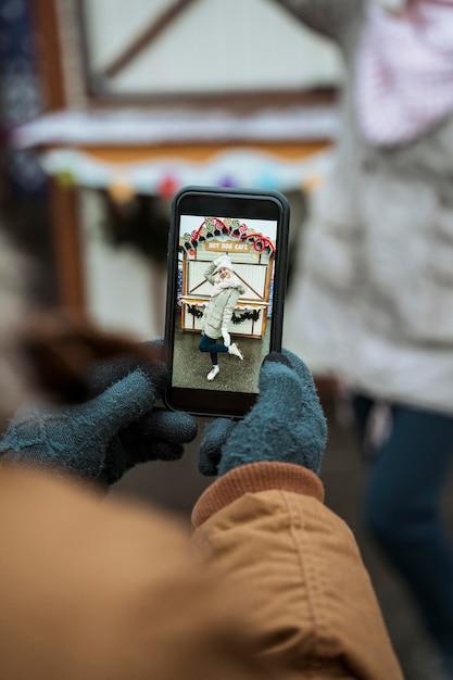 Pessoa tirando a foto de uma mulher ao ar livre Foto gratuita