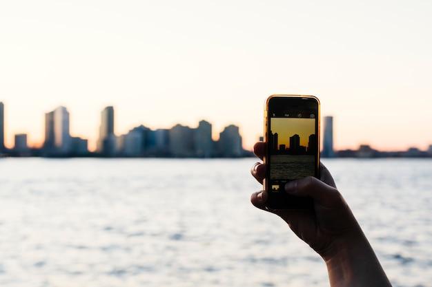 Pessoa tirando foto do pôr do sol da cidade em smartphone Foto gratuita
