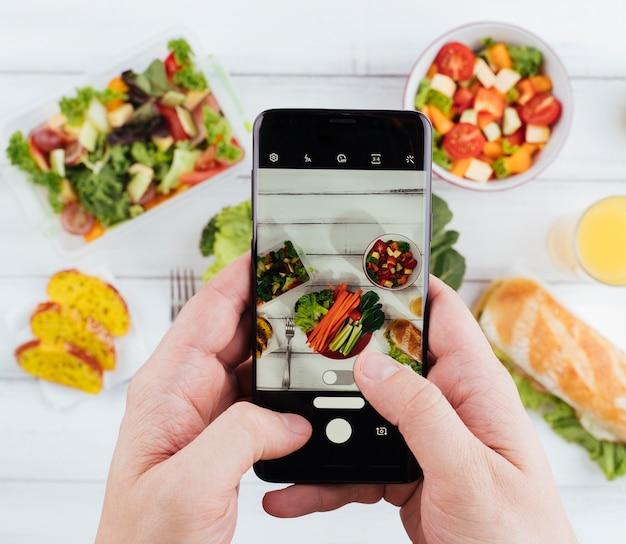 Pessoa tirando uma foto de comida deliciosa e saudável Foto gratuita