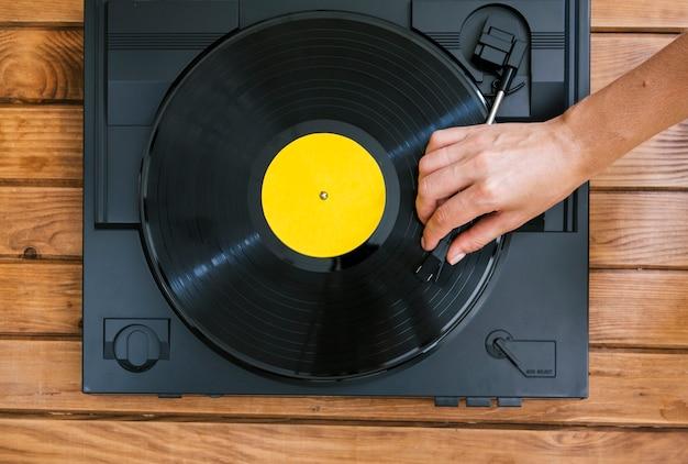 Pessoa tocando um disco de vinil no leitor de música vintage Foto gratuita