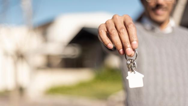 Pessoa turva, segurando as chaves da casa vista frontal Foto Premium