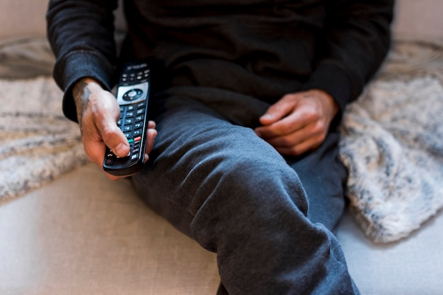 Pessoa usando o controle remoto enquanto está sentado no sofá Foto gratuita