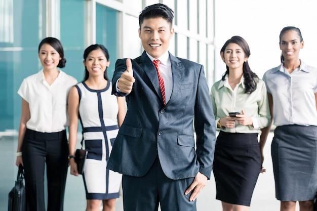 Pessoal do banco na frente do escritório, mostrando os polegares para cima Foto Premium