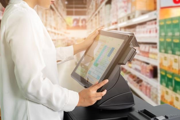 Pessoal fêmea do caixa que está e que trabalha com a máquina da posição ou do ponto de venda no contador no supermercado. Foto Premium