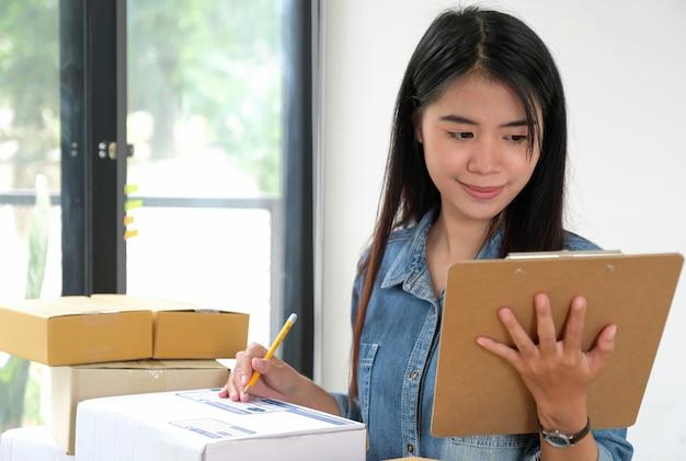Pessoal feminino, mantendo os arquivos na mão, verificando o pacote. Foto Premium