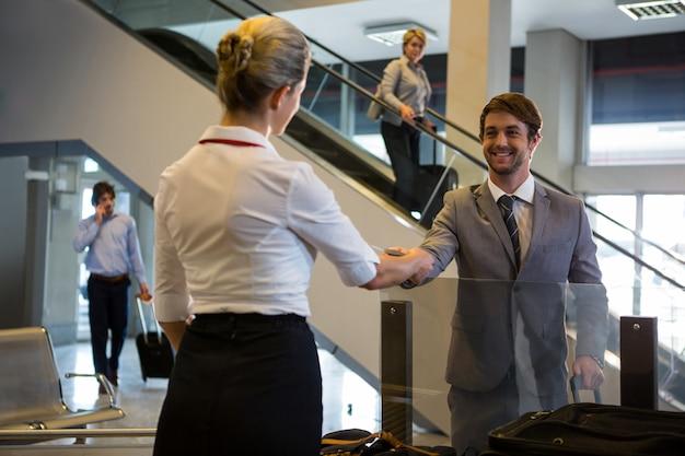 Pessoal feminino, verificando o cartão de embarque de passageiros no balcão de check-in Foto gratuita