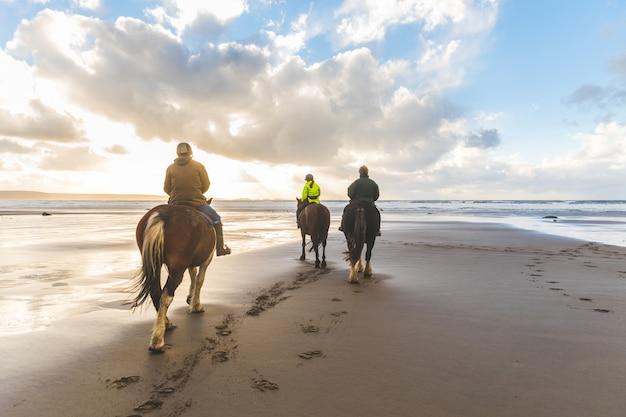 Pessoas a cavalo na praia Foto Premium