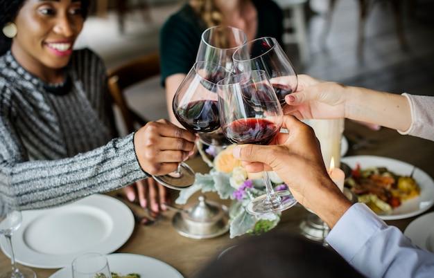 Pessoas, agarrando-se copos de vinho juntos no restaurante Foto Premium