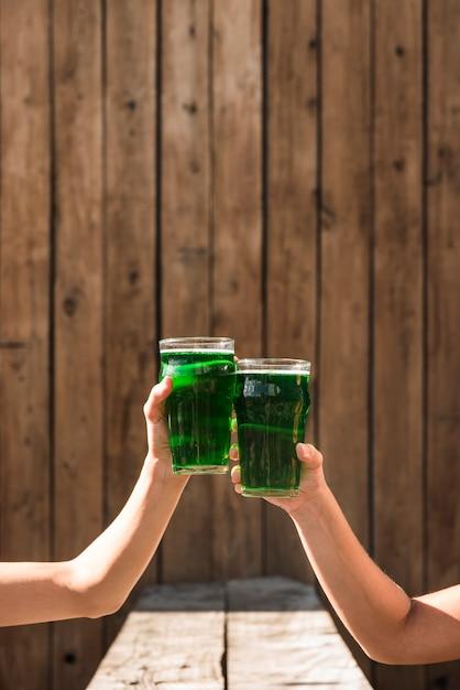 Pessoas batendo copos de bebida verde perto da mesa Foto gratuita