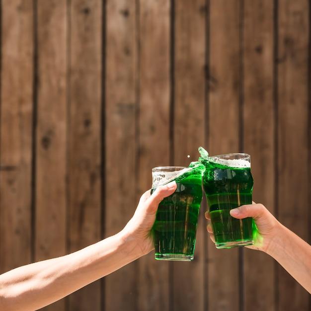 Pessoas batendo copos de bebida verde perto da parede de madeira Foto gratuita