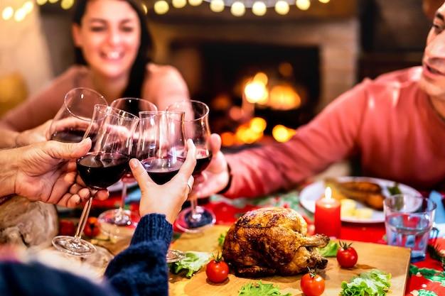 Pessoas brindando vinho tinto se divertindo no jantar de natal Foto Premium