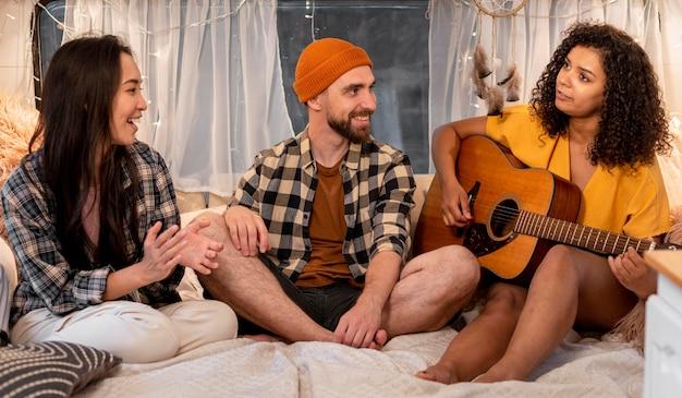 Pessoas cantando o conceito de viagem de aventura dentro de casa Foto gratuita