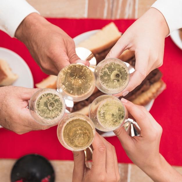 Pessoas, clanging, taças champanha, em, festivo, tabela Foto gratuita