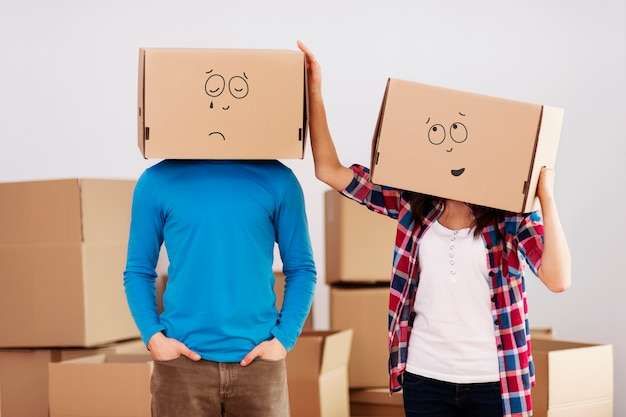Pessoas com caixas de papelão na cabeça Foto gratuita