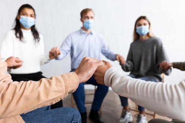 Pessoas com máscaras médicas de mãos dadas em sessão de terapia de grupo Foto gratuita