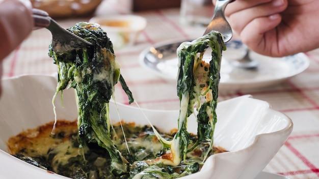 Pessoas comendo espinafre queijo assar receita Foto gratuita