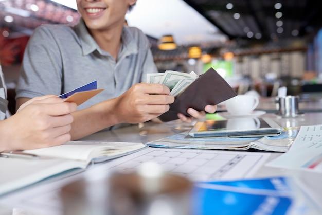 Pessoas cortadas, verificando sua carteira por dinheiro e cartão bancário Foto gratuita
