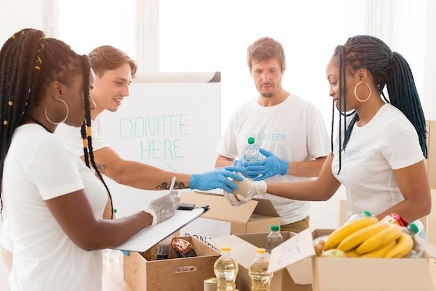 Pessoas cuidando juntas das doações Foto gratuita