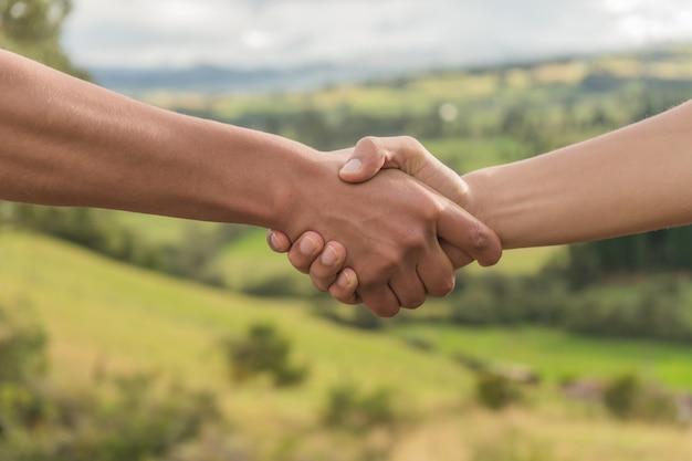 Pessoas cumprimentando, apertando as mãos na natureza, pôr do sol aperto de  mão | Foto Premium