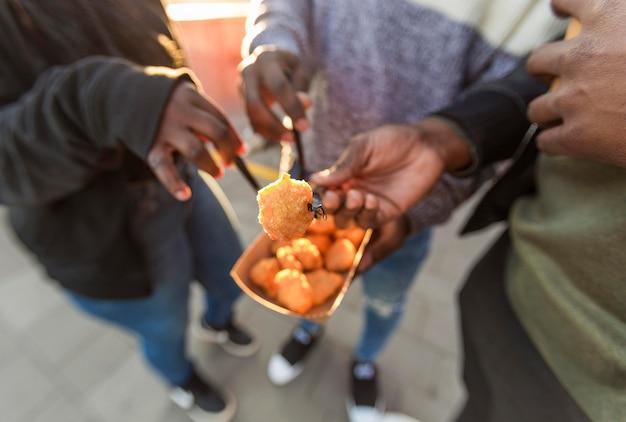 Pessoas de alto ângulo comendo nuggets de frango em embalagens de comida para viagem Foto gratuita