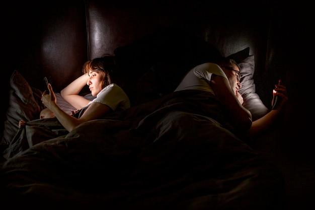 Pessoas de alto ângulo na cama com smartphones Foto gratuita