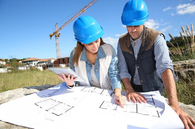 Pessoas de construção olhando planta Foto Premium