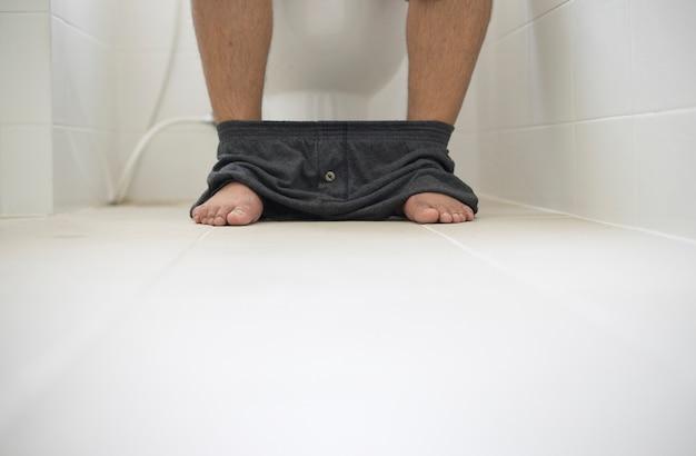 Pessoas de foco seletivo sentado no vaso sanitário Foto Premium