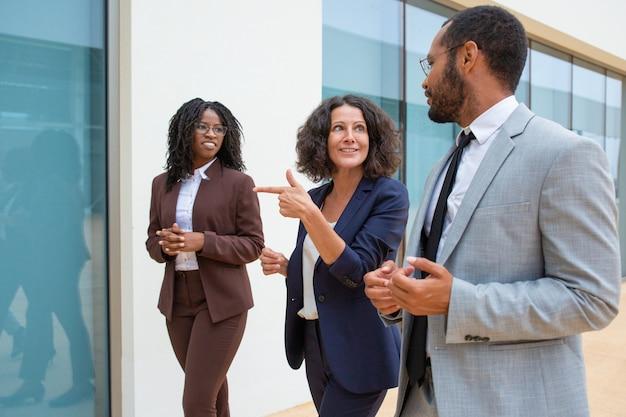 Pessoas de negócios alegres andando e conversando Foto gratuita