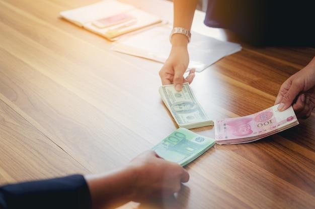 Pessoas de negócios com dólares em dólares, rmb yuan, compartilhamento de dinheiro em euros para investimentos em câmbio Foto Premium