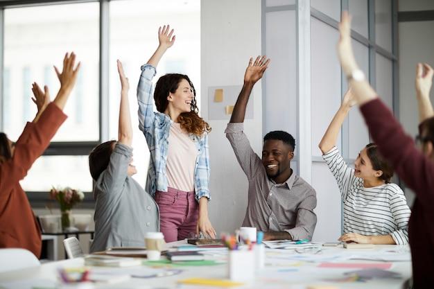 Pessoas de negócios contemporâneas, levantando as mãos Foto Premium