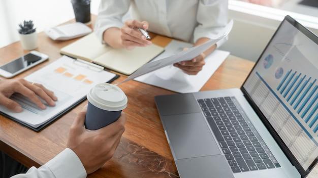 Pessoas de negócios conversando discutindo com o colega de trabalho, analisando tabelas e gráficos de dados de documentos financeiros Foto Premium