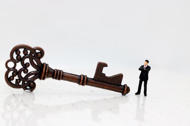 Pessoas de negócios em miniatura com a chave do sucesso Foto Premium