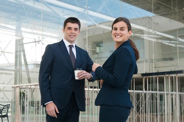 Pessoas de negócios feliz bebendo café e posando ao ar livre Foto gratuita