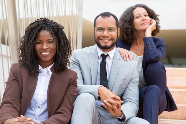 Pessoas de negócios feliz sentado nos degraus Foto gratuita