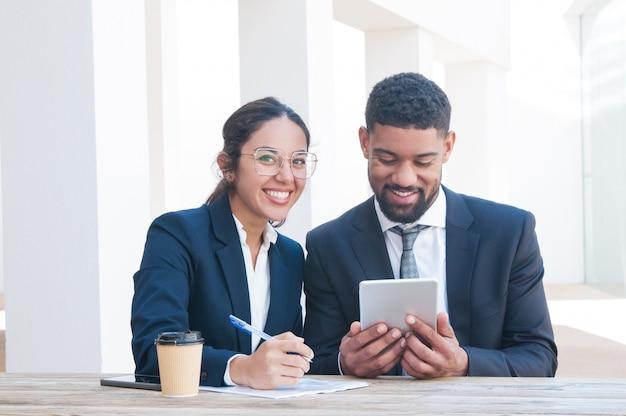 Pessoas de negócios feliz usando tablet e trabalhando na mesa Foto gratuita
