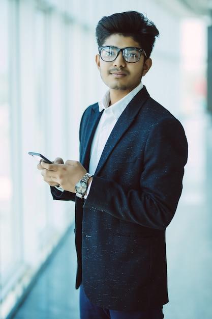 Pessoas de negócios indianos asiáticos mensagens de texto usando smartphone enquanto caminhava no escritório moderno Foto gratuita