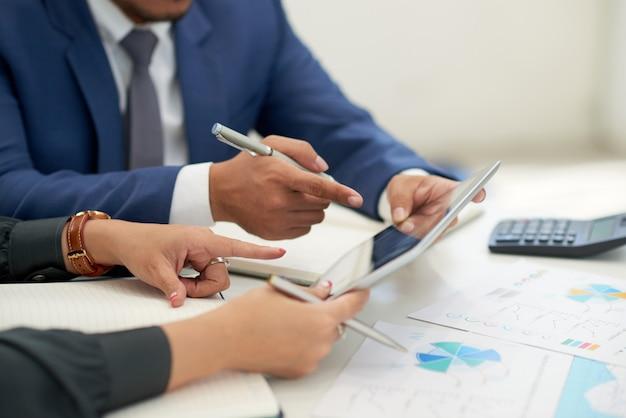 Pessoas de negócios irreconhecíveis, sentado na reunião com gráficos, olhando e apontando para tablet Foto gratuita