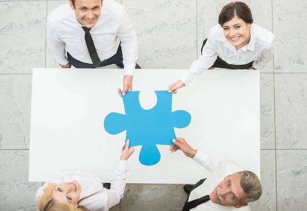 Pessoas de negócios, mantendo grande pedaço de quebra-cabeça juntos. Foto Premium