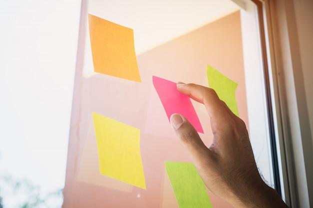 Pessoas de negócios mãos postar papel de nota pegajosa na placa de programação lembrete de vidro Foto Premium