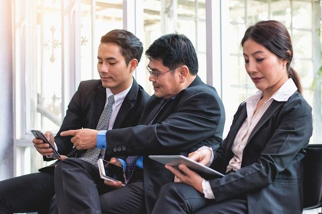 Pessoas de negócios olhando e sorrindo conteúdo no celular Foto Premium