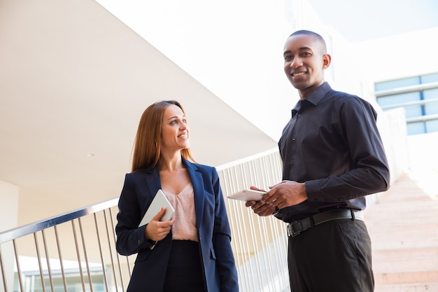 Pessoas de negócios positivos falando e segurando tabuletas nas escadas Foto gratuita