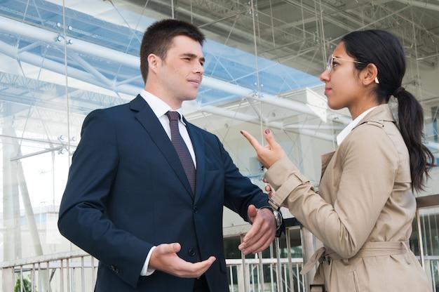 Pessoas de negócios sérios, gesticulando e discutindo questões ao ar livre Foto gratuita
