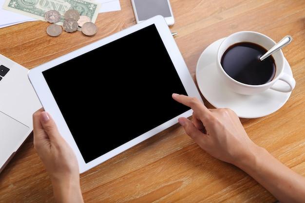 Pessoas de negócios usam maquete do tablet com artigos de papelaria do escritório e café preto na mesa de madeira Foto Premium
