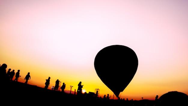 Pessoas de silhueta e balões de ar quente no festival de balão Foto Premium