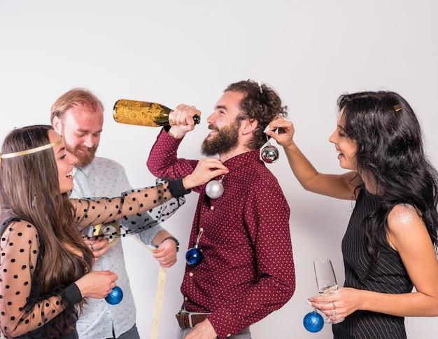 Pessoas, decorando, homem, com, brilhante, baubles, enquanto, ele, bebendo Foto gratuita