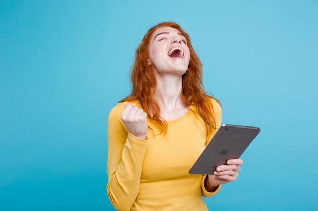 Pessoas e conceito de tecnologia - close up retrato jovem atraente atraente redhair menina feliz sorrindo na mesa digital com ganhar algo. fundo pastel azul. copie o espaço. Foto gratuita