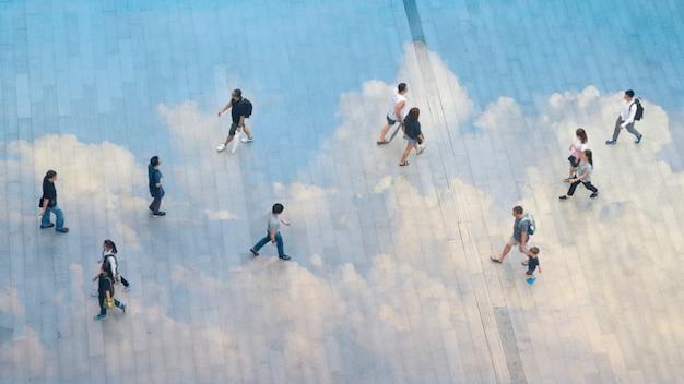 Pessoas e grupo familiar e criança andar em toda a paisagem de concreta pedestre com refletem nuvem. Foto Premium
