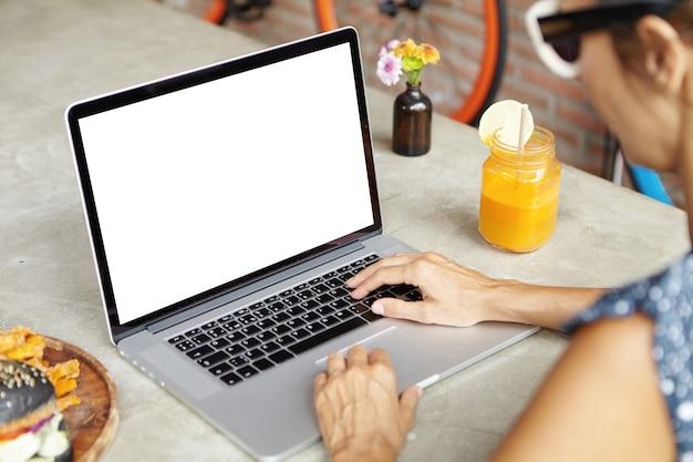 Pessoas e tecnologia. mulher em tons de navegação na internet em seu laptop genérico, teclado Foto gratuita