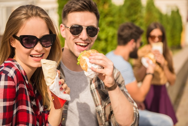 Pessoas em copos estão comendo fast food. Foto Premium